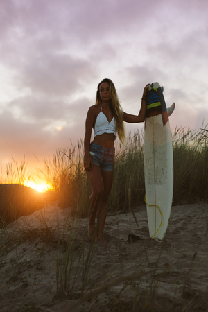 Young beautiful surfer standing at the beach with her surfboard in the morning against the sunrise. Natural girl on her way to the sea for surfing. Playa de Salinas, Asturias, Spain.
