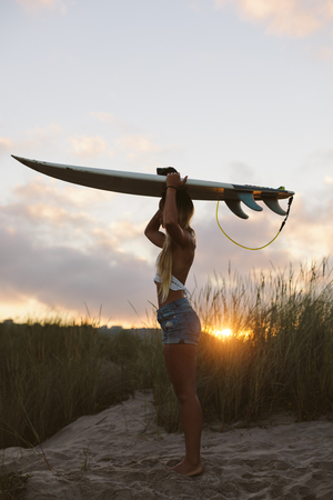 Young woman standing in the beach holding her surfboard over her head against morning sunrise. Surfer backlit by the sun. Natural girl on her way to the sea for surfing. Playa de Salinas, Asturias, Spain.