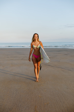 Beautiful happy young surfer walking at the beach with her surfboard. Surfing lifestyle. Playa de Salinas, Asturias, Spain. Stock Photo