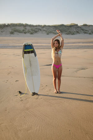 Surfing lifestyle. Young fit surfer in bikini with her surfboard at the beach. Playa de Salinas, Asturias, Spain.