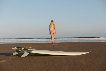 Back view of young female surfer towards the sea. Focus on surfboard. Surfing lifestyle concept. Stock Photo