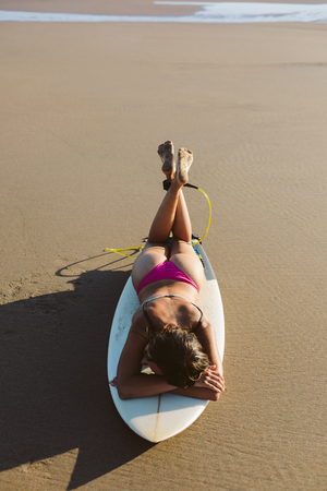 Young relaxed surfer lying on surfboard for resting after summer morning surfing session. 写真素材