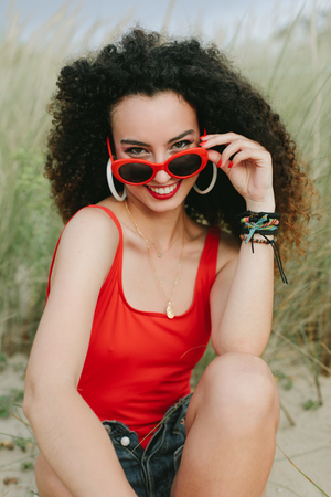 Retro pop summer fashion. Young curly hair girl wearing red sunglasses and smiling at the beach.