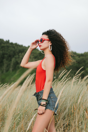 Retro pop summer style. Young curly hair girl wearing red sunglasses at the beach.
