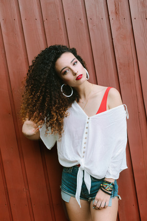 80s retro looking girl touching her curly hair. Summer pop fashion look.