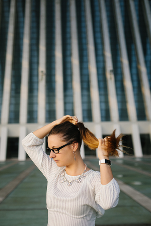 Young professional woman lacing ponytail outside corporate building. Female business style.