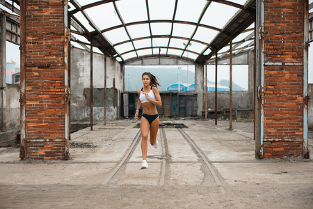 Young female athlete running at old industrial ruins. Sporty fit woman training outdoor.