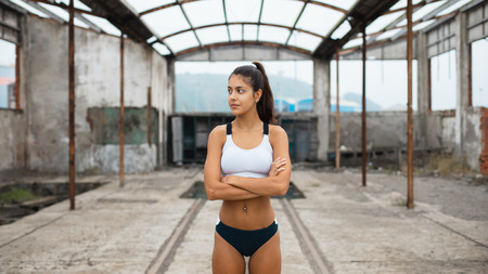 Motivated young female athlete taking a break during outdoor running workout at abandoned industrial ruins. Stock Photo