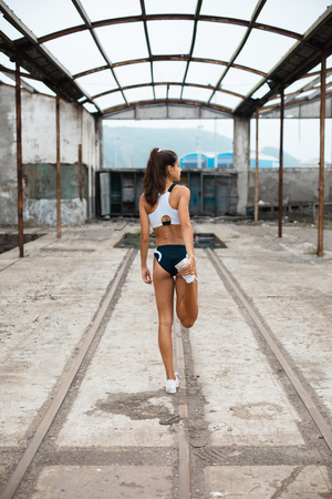 Young fit female runner stretching legs for warming up before running workout. Sporty girl exercising at old urban ruins of industrial area.