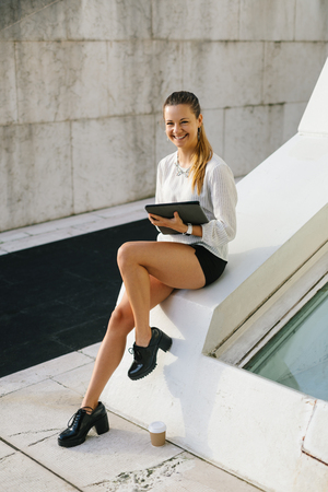 Young stylish professional woman working outside with digital tablet during coffee break. Stock Photo