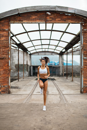 Young female athlete doing technique running in place exercise at old industrial ruins. Sporty fit woman skipping outdoor. Stock Photo