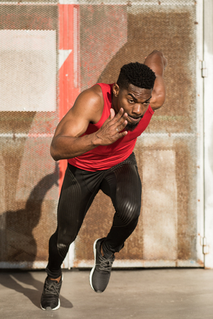 Young black urban athlete running and sprinting. Stock Photo