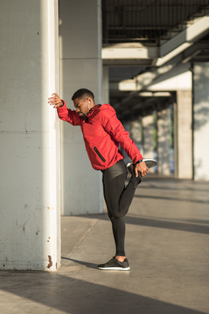 Black runner doing stretching exercise for warming up. Stock Photo