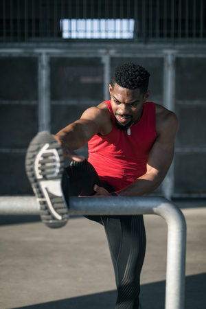 Urban athlete exercising and stretching legs. Stock Photo