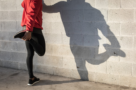 Cast shadow of athlete stretching quadriceps during running urban workout.