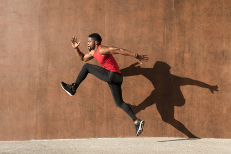 Young black man running and jumping casting shadow on a wall. Stock Photo