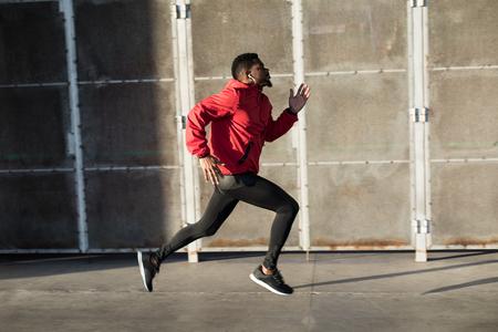 Junger schwarzer Mann, der schnell in der Stadt läuft. Standard-Bild
