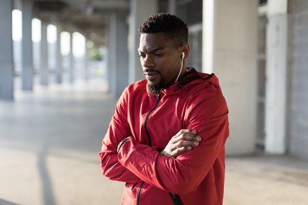 Portrait of motivated sportsman listening music during urban outdoor workout.