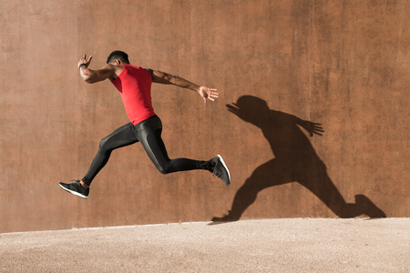 Young black man running and jumping casting shadow on a wall. 스톡 콘텐츠