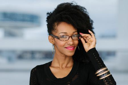 Young cheerful urban stylish businesswoman wearing glasses.