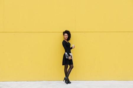 Stylish businesswoman on coffee break outside against yellow wall.