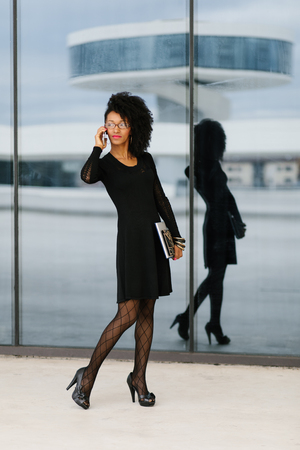 Young stylish urban businesswoman talking on mobile phone.