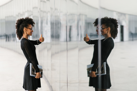 Successful stylish businesswoman doing thumbs up gesture to herserlf in glass reflection. Фото со стока - 120552027