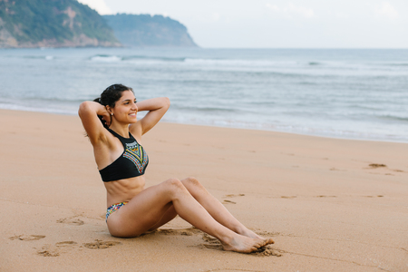 Cheerful fit young woman in bikini doing sit-ups at the beach. Outdoor fitness and healthy lifestyle. Stock Photo