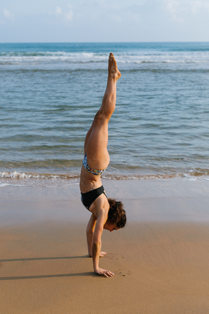 Fit young woman in bikini doing headstand gymnastic balance exersice at the beach. Outdoor fitness and healthy lifestyle.