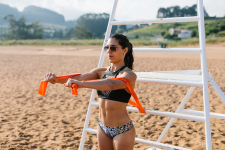 Fit young woman in bikini exercising at the beach with resistande band. Summer healthy outdoor fitness workout.