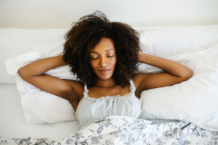 Young relaxed woman sleeping in the bed in the morning. Blissful black model. Tranquility and leisure at home concept.