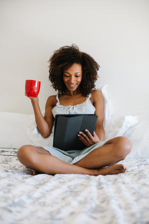 Young relaxed woman at home reading on digital tablet and drinking coffee in her bed in the morning. Afro hair black beautiful model.