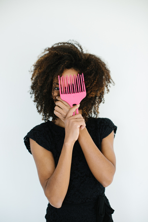 Pretty afro hairstyle woman using comb for untangle her curly hair. Black female beauty and style tips concept. Banco de Imagens