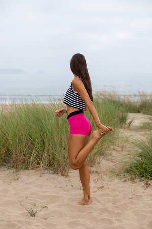 Young sporty woman ath the beach doing quadriceps stretching exercise for warming up before running. Summer fitness lifestyle motivation.