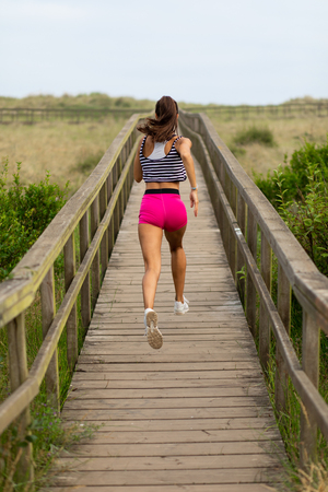 Summer running outdoor workout. Fitness lifestyle and exercising. Back view of young female runner training.