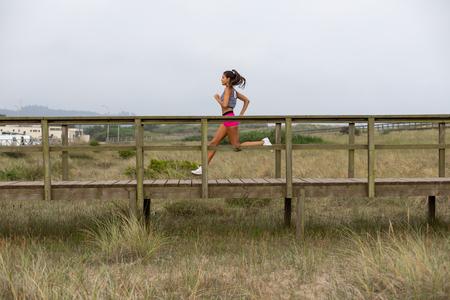 Young female runner training. Summer running outdoor workout. Fitness lifestyle and exercising. San Juan de Nieva, Asturias, Spain.