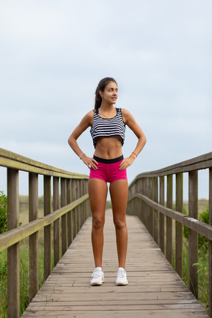 Summer fitness lifestyle motivation. Young sporty woman taking an outdoor running workout rest.