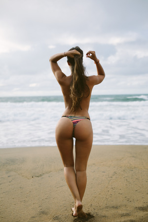 Back view of woman at beach towards the sea. Summer vacation relax and female freedom concept.