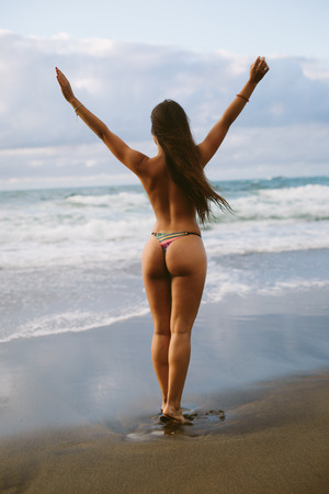 Back view of topless woman raising arms at the beach towards the sea. Summer vacation relax and freedom concept. 스톡 콘텐츠