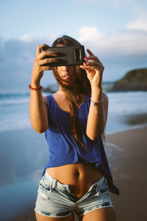 Young woman taking a selfie photo with her smartphone camera on summer vacation at the beach. Banco de Imagens