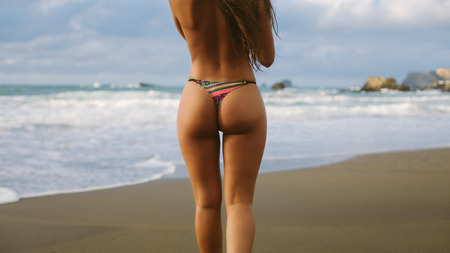 Back view of woman wearing thong at the beach towards the sea. Summer vacation relax and freedom concept. Playa de Verdicio, Asturias, Spain.