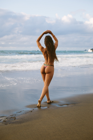 Back view of topless woman raising arms and walking at the beach towards the sea. Summer vacation relax and freedom concept. Imagens