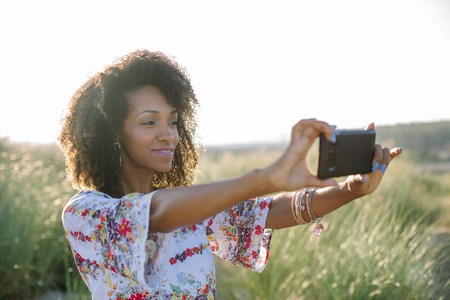 Happy young beautiful black woman using smartphone camera for taking a photo at the beach on summer or spring vacation.