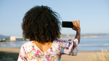 Back view of woman using smartphone for taking a photo at the beach on summer or spring vacation. Blank copy space mobile screen.