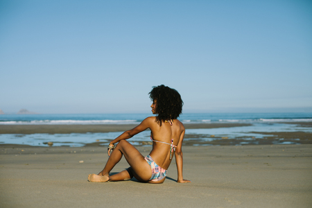 Junge schöne schwarze Frau, die sich im Sommerurlaub am Strand in Richtung Meer entspannt. Brasilianisches Modell der Afrofrisur, das ethnischen Modebikini trägt.