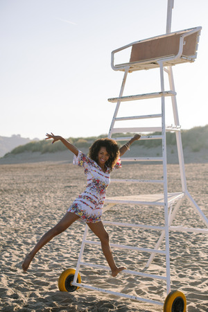 Joyful woman dancing and having fun on vacation at the beach. Spring or summer outdoor relaxing leisure. Afro hair young black female.