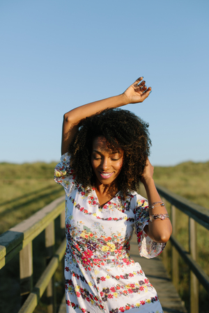 Joyful woman on spring or summer outdoor relaxing leisure. Afro hair young black female.