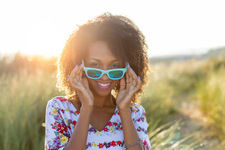 Joyful happy woman on spring or summer outdoor relaxing leisure. Afro hair young black female wearing sunglasses.