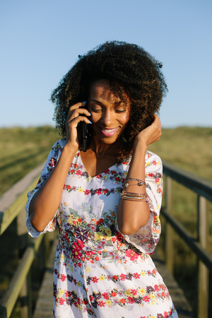 Young afro hair beautiful black woman on cell phone call outdoor. Modern mobile communication during vacation and nature activity.