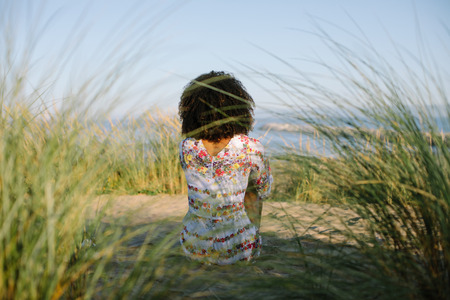 Back view of afro hairstyle black woman relaxing at the beach on summer or spring vacation.